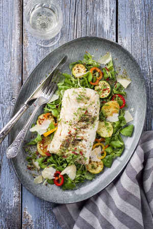 Fried cod fish fillet with lettuce and vegetable with white wine as a top view on a plate