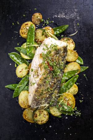 Fried cod fish fillet with vegetable and potatoes as top-view on old board