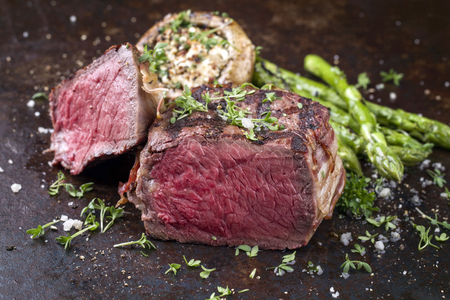 Barbecue Wagyu Point Steak with green Asparagus and Mushroom Cap as close-up on a rusty metal sheet Stock Photo