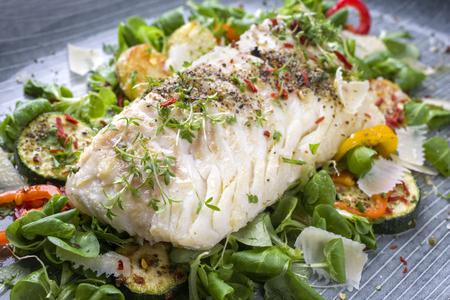 Gebakken kabeljauw visfilet met sla en groente als close-up op een bord