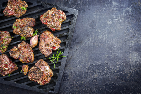 Barbecue T-bone lamb steak with seasonings as a top view on a grillage Stock Photo