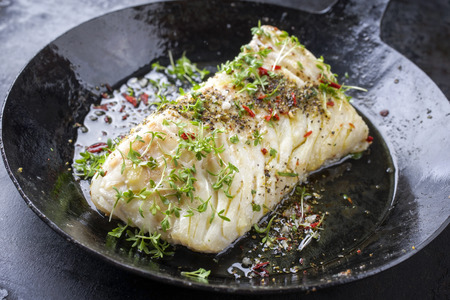Fried cod fish fillet with spice and cress as close-up in a cast iron pan Stockfoto