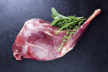 Raw Haunch of Venison with herbs as close-up on a slate slab Stock Photo