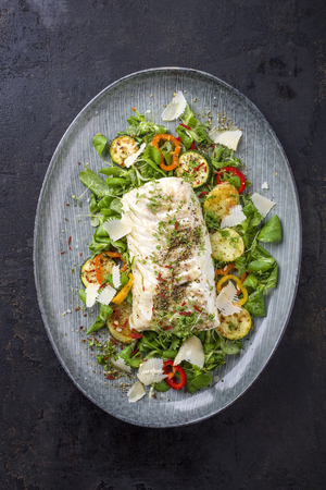 Fried cod fish fillet with lettuce and vegetable as top view on a plate