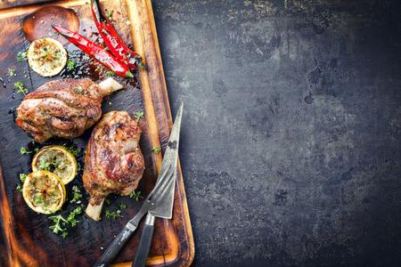 焦げたまな板の上トップ ビューとしてトマト唐辛子風味のラムのバーベキュー脚 写真素材