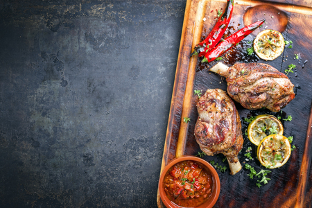Barbecue Leg of Lamb with Tomato Chili Relish as a top view on burnt cutting board Stock Photo