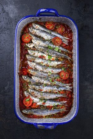Sardinas en salsa with garlic bead as top view in a skillet   Stock Photo