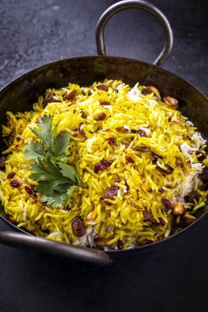 Indisches vegetarisches biryani mit Nüssen und Rosinen als Nahaufnahme in einem Korai Standard-Bild - 86898274