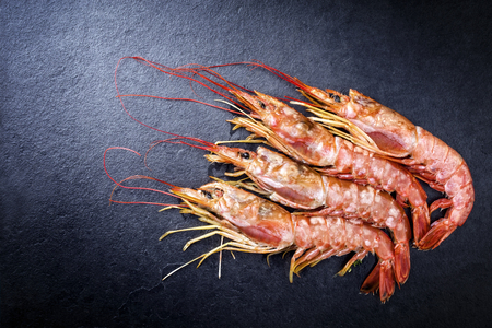 Four raw black tiger prawn as top view on a black board
