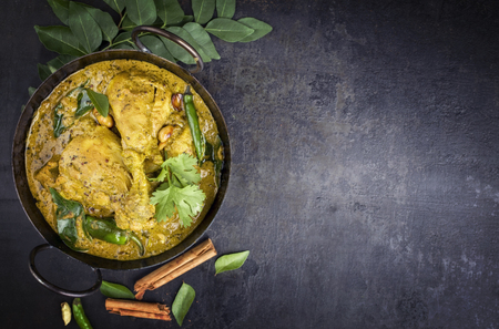 Traditional Indian curry chicken as close-up in a Korai with copy space right
