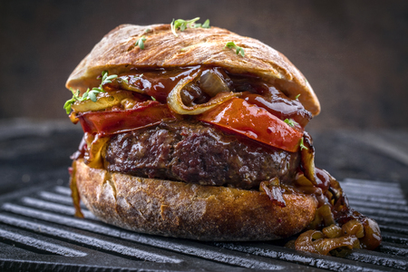 Barbecue Wagyu cheeseburger with onions and tomatoes as close-up on a grillage