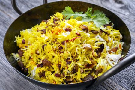 Indian vegetarian biryani with nuts and raisins as close-up in a korai