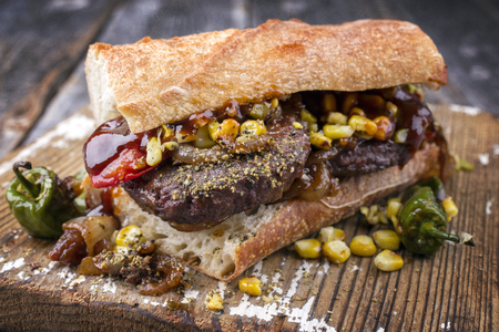 Barbecue Wagyu Hamburger with corn and tomatoes as close-up on a cutting board Stock Photo