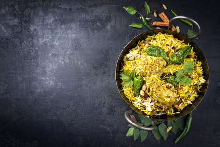 Traditional Indian chicken biryani with nuts and raisins as close-up in a korai with copy space left Stockfoto