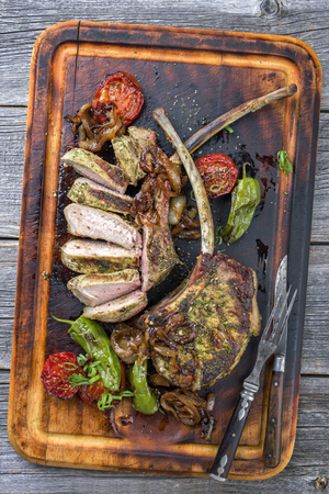 holz: Barbecue tomahawk pork steak with vegetable and onion as top view on a cutting board