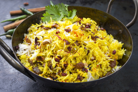 Indian vegetarian biryani with nuts and raisins as close-up in a korai