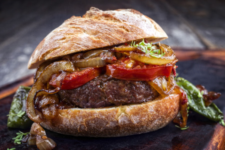 Barbecue Wagyu Hamburger with onions and tomatoes as close-up on a burnt cutting board
