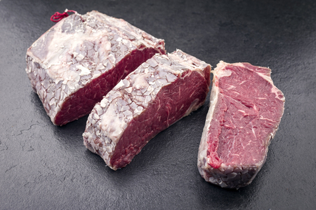 Raw dry aged Kobe Roastbeef wrapped in fat as close-up on a slate Stock Photo