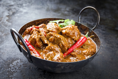 Traditional Indian curry lamb masala as close-up in a Korai  免版税图像