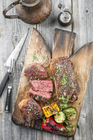 Two barbecue dry aged Kobe roast beef with vegetable as close-up on a cutting board Stock Photo