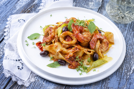Italian tagliatelle con gamberi e calamari in salsa di pomodoro with olives and peperoni as close-up on a plate