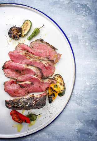 Barbecue dry aged wagyu sliced roast beef steak with vegetable as close-up on a white plate Stock Photo