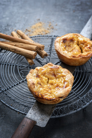 Traditional Portuguese pasteis de nata as close-up on a cooling rack