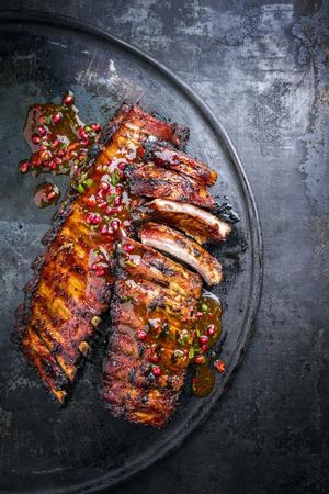 Barbecue varkensribbetjes met fruit genieten als bovenaanzicht op een oude rustieke bord Stockfoto