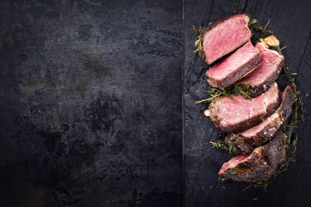 Barbecue dry aged Kobe rib eye steak as close-up on a burnt board with copy space left Stock Photo