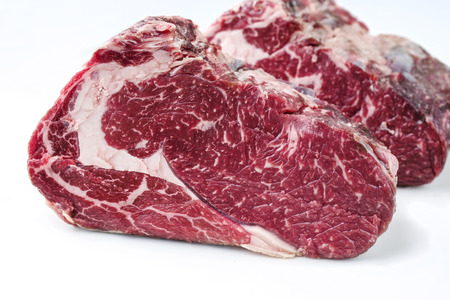 Two raw dry aged Kobe rib eye steak as close-up � covered Stock Photo