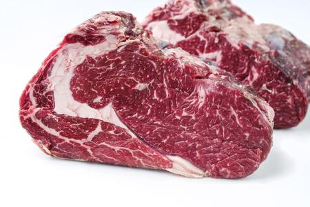 Two raw dry aged Kobe rib eye steak as close-up � covered Stock Photo