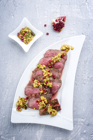 Barbecue dry aged Kobe chateaubriand steak with fruit relish as close-up on a white plate  Stock Photo