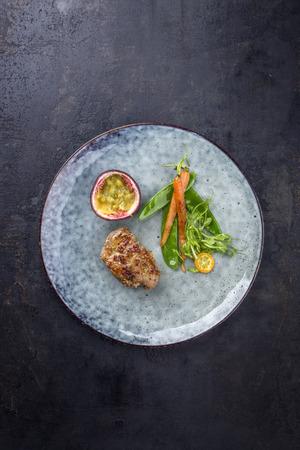 Gebratenes Schweinefilet mit Gemüse und Passionsfrucht als Draufsicht auf einem Teller Standard-Bild - 94523527
