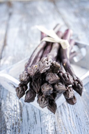 Row purple Asparagus as close-up in a tray  Stock fotó