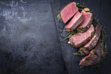 Barbecue dry aged Kobe rib eye steak as close-up on a burnt board with copy space left  Foto de archivo