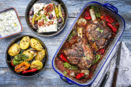 Greek roasted leg of lamb with feta and potatoes in tomato sauce as top view in a skillet  Stock Photo