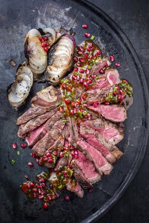 Barbecue dry aged caveman wagyu porterhouse steak with onion and pomegranate salsa as top view on a board