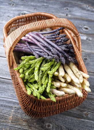 Fresh raw white, green and purple asparagus as top view in a basket Stock Photo