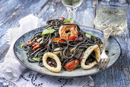 Italian linguine con tinta de calamari and prawns with olives as close-up on a plate  Stock Photo