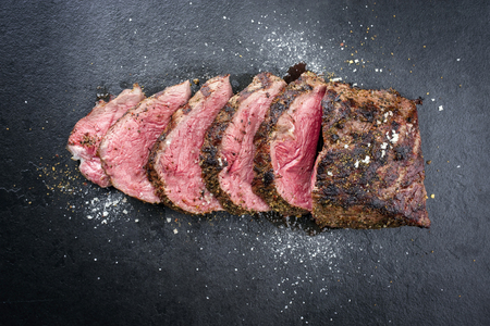 Barbecue dry aged caveman wagyu chateaubriand steak sliced as close-up on a board  Stockfoto