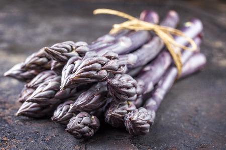 Row purple Asparagus as close-up on an old metal board with copy space