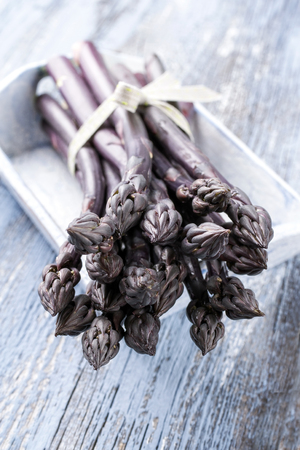 Row purple Asparagus as close-up in a tray  Stock Photo