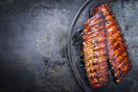 Barbecue pork spare ribs as top view on an old rustic board Stock Photo