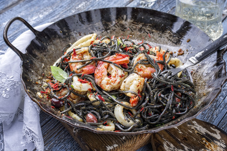 Italian linguine con tinta de calamari and prawns with olives as close-up in a wroth iron pan Stock Photo