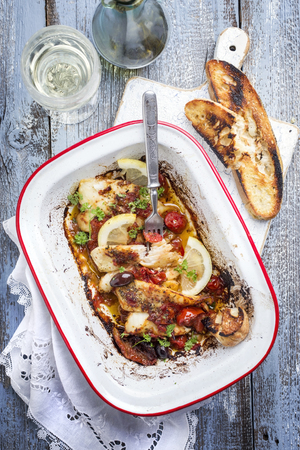 Fried John Dory fish fillet with vegetable and baguette as top-view in a roasting tin