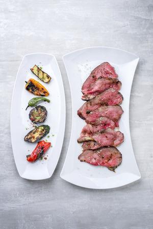 Barbecue trocken gealtert Wagyu geschnittenem Roastbeef Steak mit Gemüse als Nahaufnahme auf einem weißen Teller Standard-Bild - 94523731