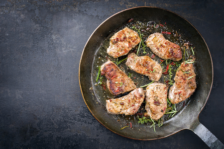 Fried saddle of pork steak with herb as top view in a frying pan with copy space left Standard-Bild - 94523753