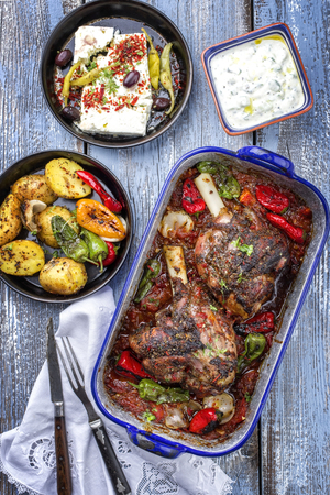 Greek roasted leg of lamb with feta and potatoes in tomato sauce as top view in a skillet