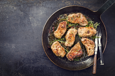 Fried saddle of pork steak with herb as top view in a frying pan with copy space left