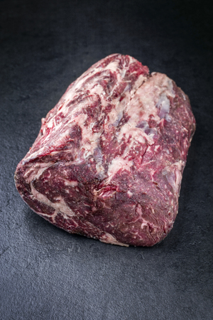 Raw dry aged Kobe rib eye steak as close-up on a black board  Reklamní fotografie